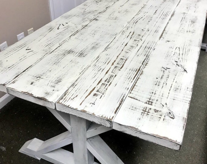 Weathered White Pedestal Farmhouse Table whith Distressed White Trestle Base and Weathered Top with Dark Walnut Showing Through Dining