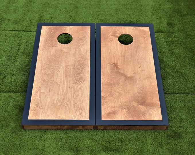 Cornhole Boards with a light stain and Black border with bags