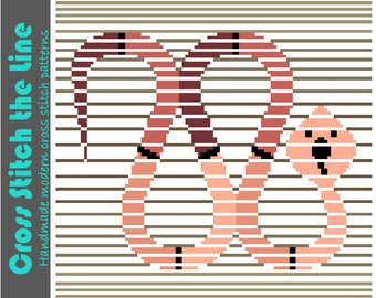 Contemporary cross stitch pattern of a snake in the sand. Modern design. Minimalist embroidery chart.