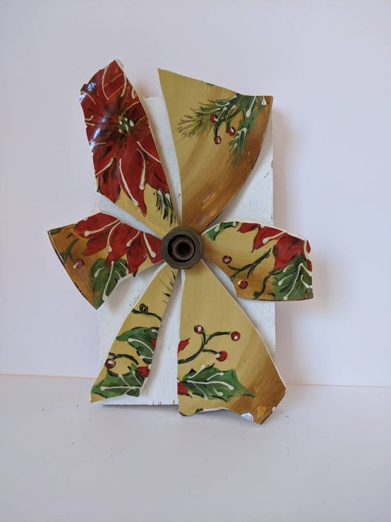 This broken and beautiful flower, made with red green and tan pottery, has a vintage hardware center and is mounted on white reclaimed wood.