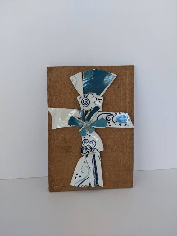 This broken and beautiful cross is made with aqua and white floral dinner plates. There is a sweet blue flower in the center.