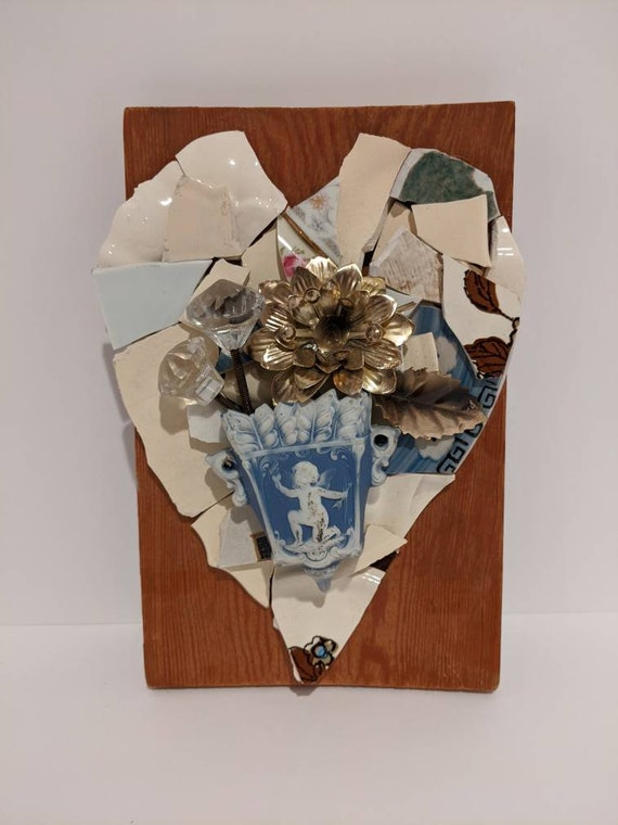 Broken and beautiful mixed media, wall mounted heart collage with broken ceramics vintage hardware and other found items.
