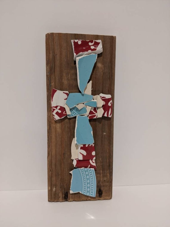 Broken and beautiful cross made with different patterns of aqua and red & white floral dinner plates.