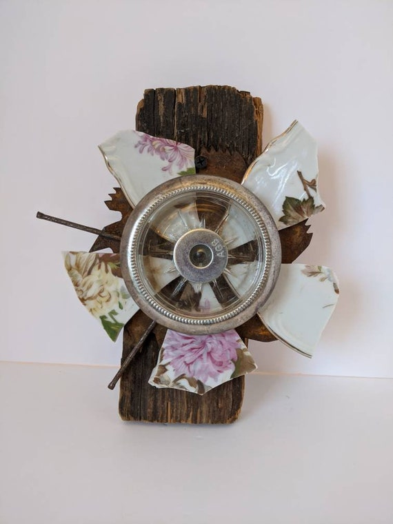 This broken and beautiful flower is made with pink floral China, a vintage coaster and an old circular saw blade, mounted on reclaimed wood