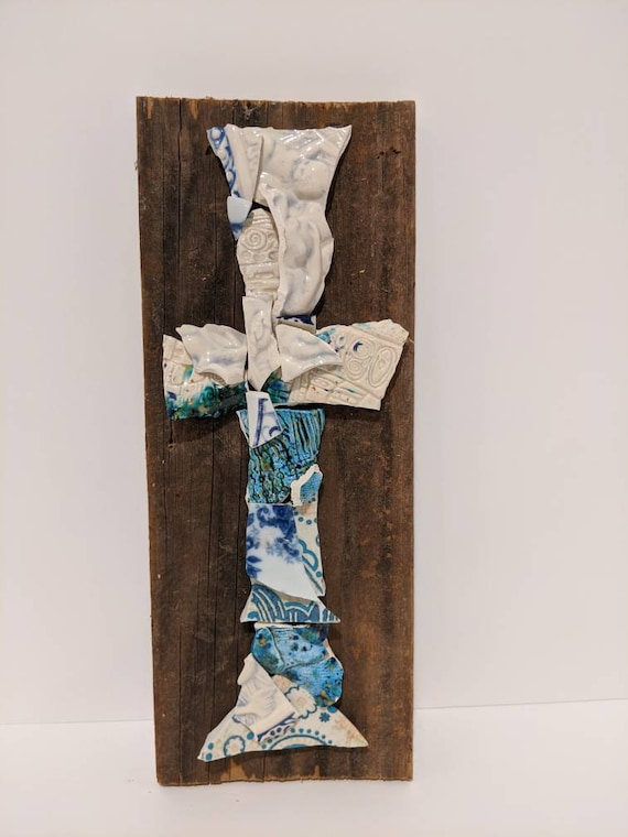 This broken and beautiful cross is made with broken plates in aquas and blues, and white textured pottery