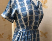 1950s nos with tags silk coat of arms fabric pattern dress with pleated skirt.