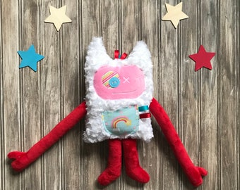 Cuddle Monster plush toy Monstre à Câlins with horns and a secrets or kisses pocket with a rainbow, soft plush hugging friend