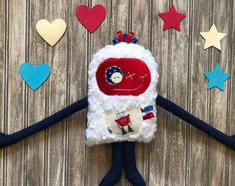 Cuddle Monster (Monstre à Câlins) plush toy with ribbons on the head,  bleu and red with robot on the pocket