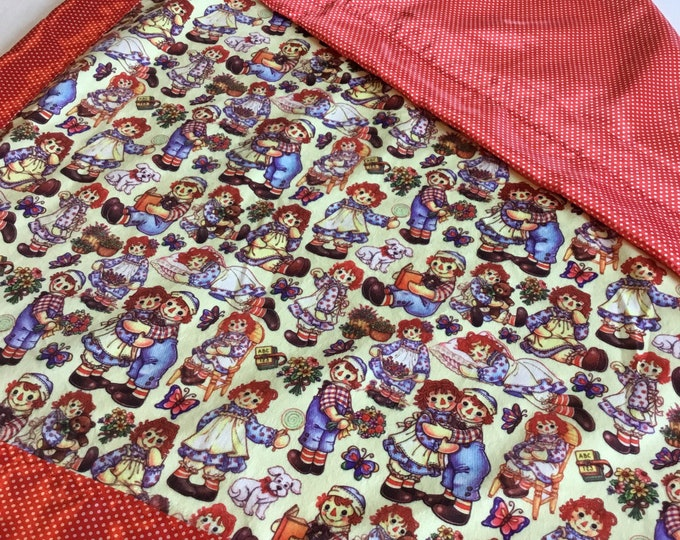 Raggedy Ann and Andy baby blanket.. approximately 36x30. Light weight cozy raggedy ann and andy front, backed and edged with pin dor silky