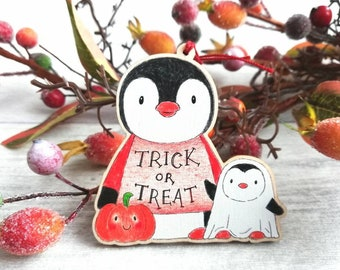 Trick or treat penguins tag. Wooden Halloween decoration. Ghost and pumpkin hanger ornament, eco friendly