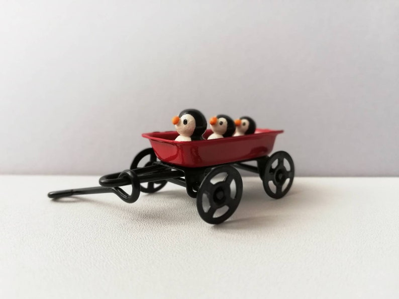 Penguins in a cart. Little pottery penguin in a mini red image 0