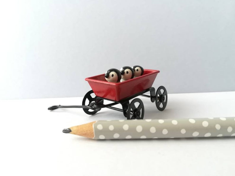 Miniature penguins in a cart. Little pottery penguin chicks in image 0