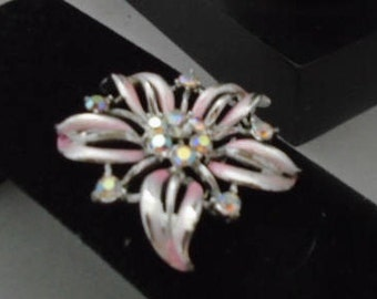 Vintage Silvertone and Pink Pin w/Rhinestones in Center. There is a Round Centerpiece w/Rhinestones. Shaped like a Flower!