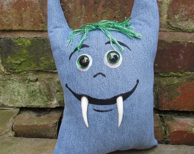 Toothy Pillow Monster of upcycled denim, with googly eyes and sculpted teeth