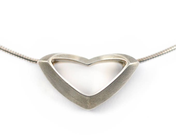 Stylized stg sil 15gm, hand-made from solid sterling silver rhodium plated, on a solid sterlin silver chain.Simplicity & beauty.