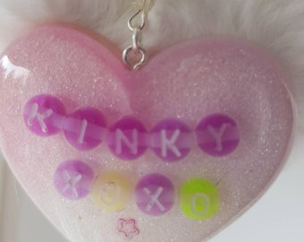 Pastel resin heart on fluffy pompom with word beads and embellishments. Ddlg babygirl alternative bdsm