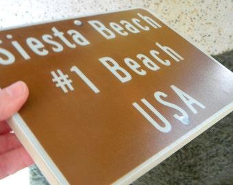 Siesta Beach #1 sign - photo on wood