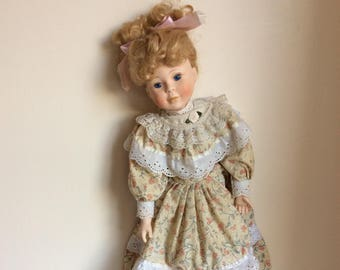French bisque doll, a collectible vintage doll with blue eyes and curly blond hair from the 1970s