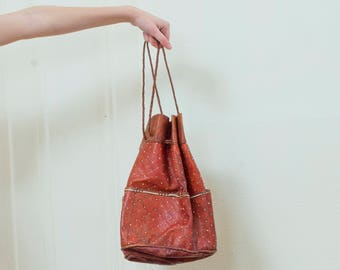 vintage brown tooled leather bag | drawstring embossed leather hobo handbag | braided leather pocket shoulder bag round | 1970s | 70s