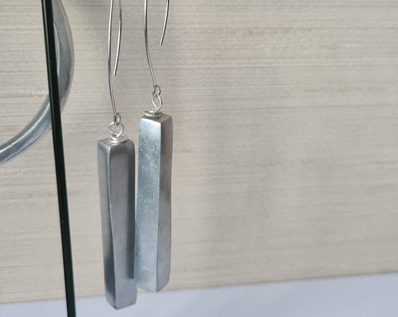 Earrings with a contemporary style, in recycled aluminum. Silver pendant earrings, rhodium drop hook. Modern and binders.
