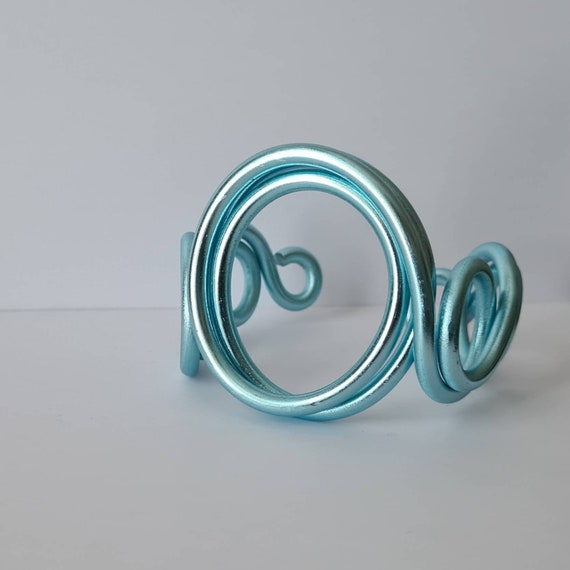 Band bracelet in light blue aluminum. Modern bracelet with an abstract, artistic design. Unconventional and elegant.