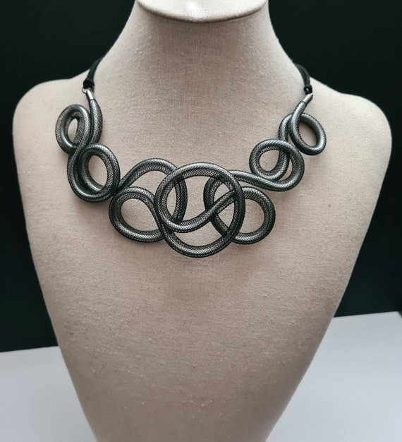 Particular necklace with a refined and extravagant style, made with silver aluminum thread and black mesh. Unusual and original.
