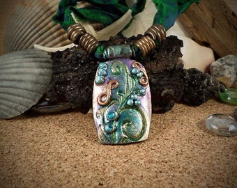 Polymer Clay Pendant with blues, greens and violet swirls.