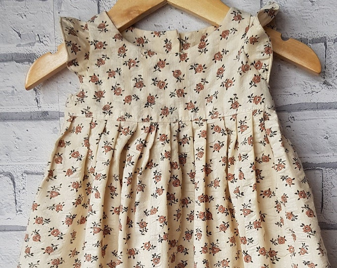 Baby/toddler dress, handmade, soft cream textured cotton with small brown print flower.  Pretty fabric and design.  One only.