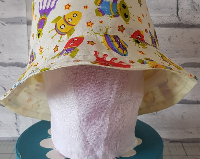 Child's reversible cotton sunhat with aliens and rockets print on one side and toning yellow on the reverse.  To fit age 6-12 months