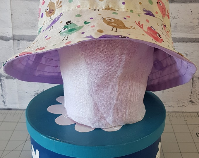 Child's reversible cotton sunhat with bird print on one side and toning lilac on the reverse.  To fit age 1-3 years.