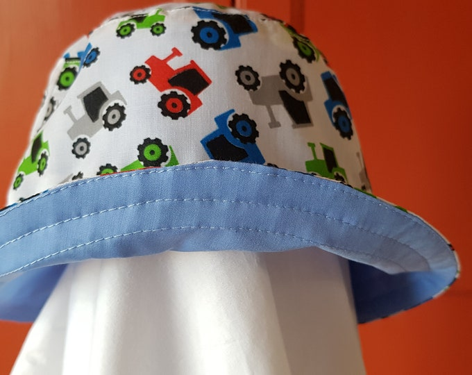 Child's reversible cotton sunhat with tractor print on one side and toning blue on the reverse.  To fit age 1-3 years.