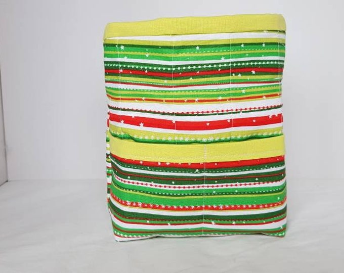 Decorative storage basket approx  20cm high x 15cm wide and 13cm diameter.   Flat base and lightly padded very colourful cotton fabric.