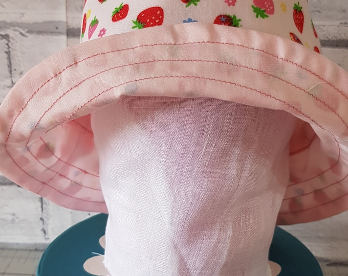 Child's reversible cotton sunhat with strawberry print on one side and toning pink on the reverse.  To fit age 6-12 months