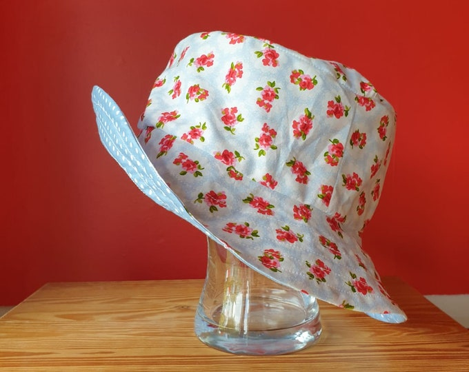 Ladies reversible sunhat in beautiful cotton fabrics, blue floral on one side and blue with white spots of the other