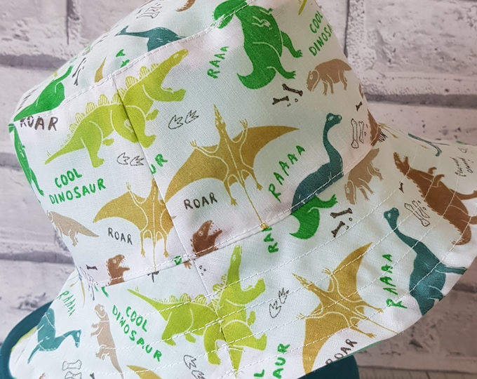 Child's reversible cotton sunhat with dinosaur print on one side and toning green on the reverse.  To fit age 1-3 years.