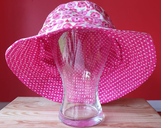 Ladies reversible sunhat in beautiful cotton fabrics, pink flowers on one side and pink with white spots on the other side.