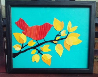 One of a kind upcycled wall art. 8x10in framed canvas created using recycled materials. Teal background, yellow leaves, red bird