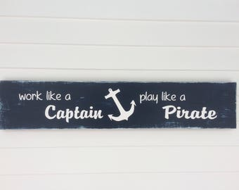 work like a Captain play like a Pirate painted wood sign.  Navy blue and white lettering and figure eight knots on each end.  Ready to ship!