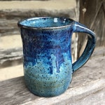 Blue pottery mug on Dark Clay with drips