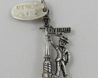 Man Holding New Orleans LA Bourbon Street Lamp With New Orleans L.A. Tag Sterling Silver Vintage Charm For Bracelet