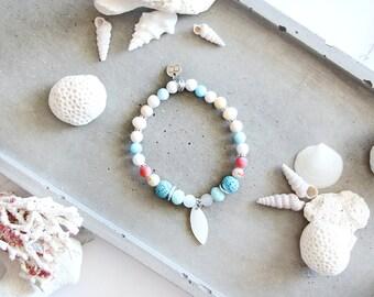 Bracelet Alizé, fil élastique, perles, bleu, crème, blanc, rosé, breloque coquillage, style plage, bijou d'été, pour femme