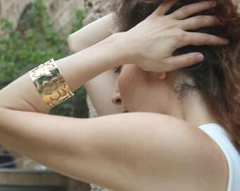 A gold daffodils wide adjustable cuff bracelet
