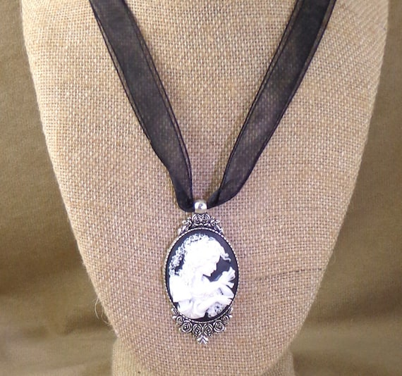 Cameo in silver toned setting, on ribbon necklace. Classic black and white cameo on black ribbon with silver tone clasp, Victorian necklace
