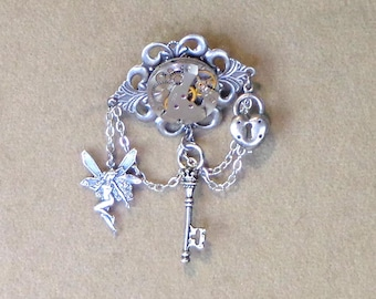 Clockwork Brooch, steampunk pin, clock parts jewelry, silver-toned filigree and watch works brooch in steampunk style, lock, key and fairy