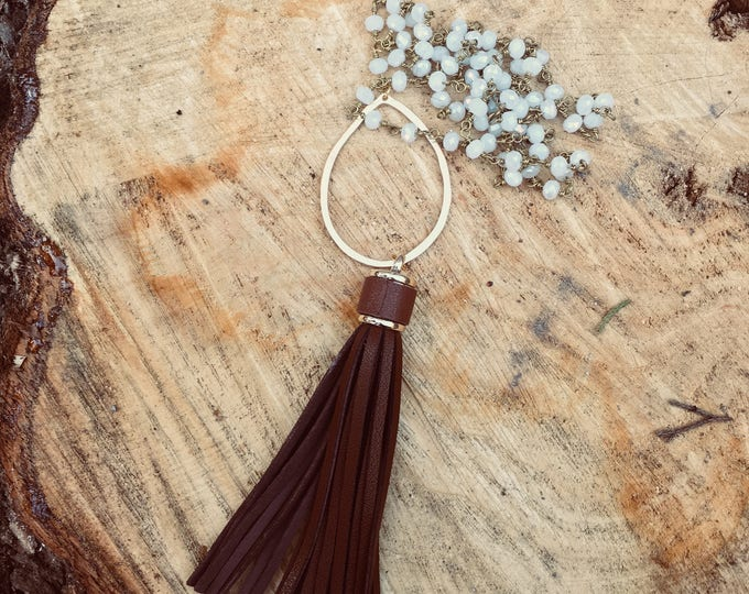 Brown Leather Tassel Necklace with a Hammered Gold Circle Pendant on an off white iridescent Beaded Chain