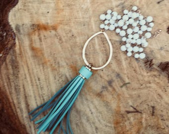 Turquoise Leather Tassel Necklace with a Hammered Gold Oval Pendant on an off white iridescent Beaded Chain
