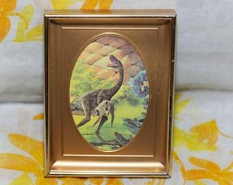 Compsognathus Holding Pterosaur in Golden Oval Frame - 4.5x6 Vintage Framed Paleoart Print - 1970s Dinosaur Illustration