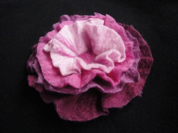 Pink wet felted flower accessory brooch or pin is made from pink dyed merino wool and has a needle felted center.