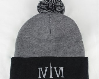 "Black/Heather Grey Toronto 416 toques. The Roman Numerals Stand For 416, With The ""1"" Resembling The CN Tower."