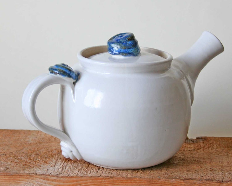 Teapot pure white with blue detail on the lid and handle. image 0